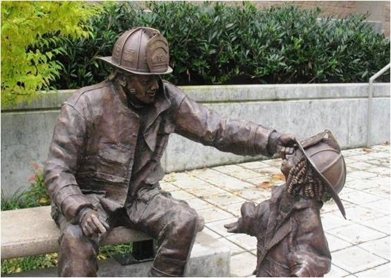 Legacy Statue - Firefighter Placing a Helmet on a Young Girl's Head