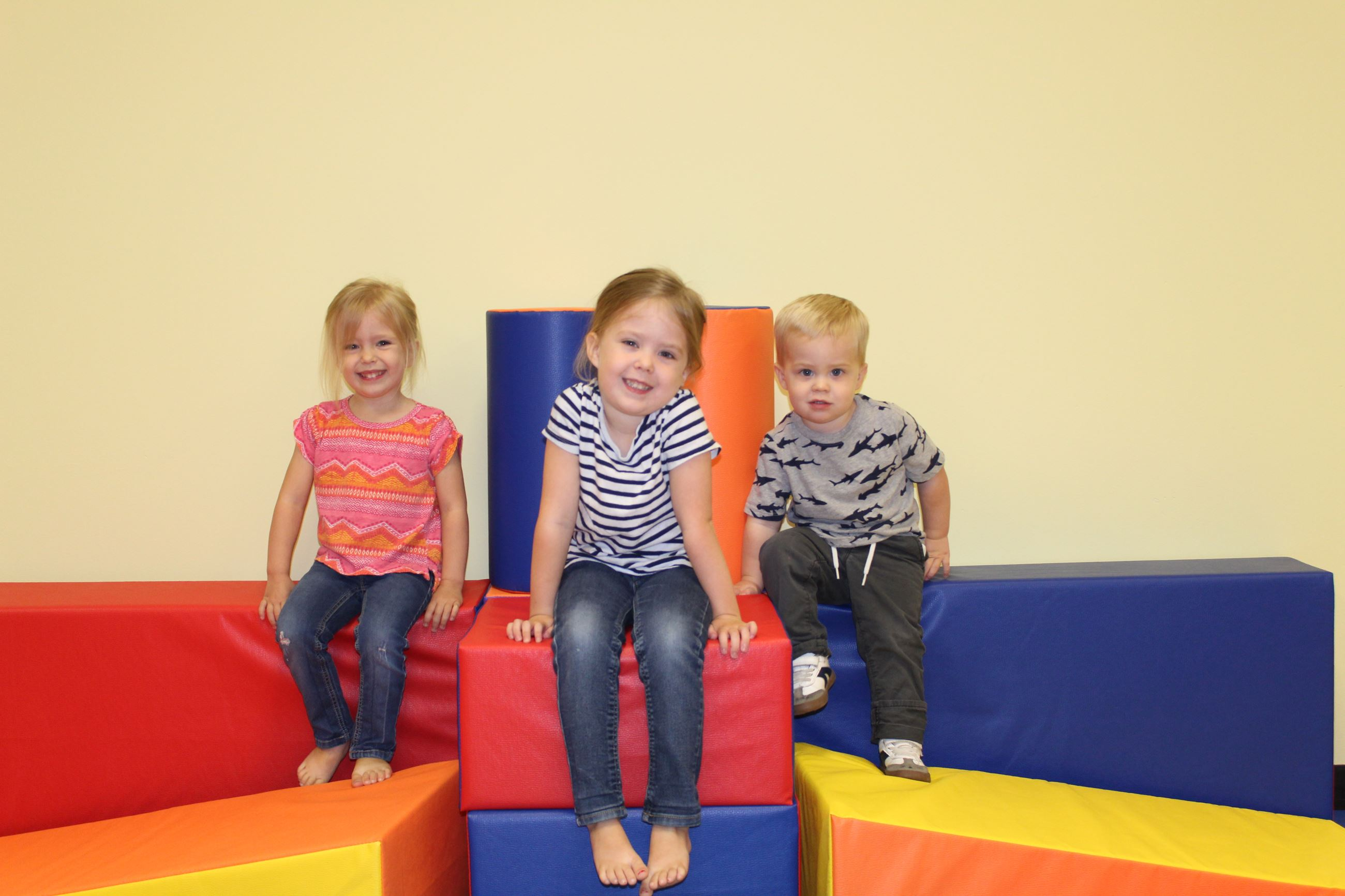 Three children sitting on foam blocks in indoor playground