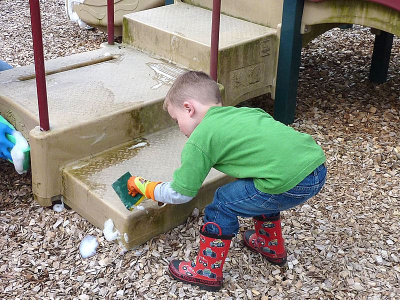 Little boy doing his part to clean up play equipment.