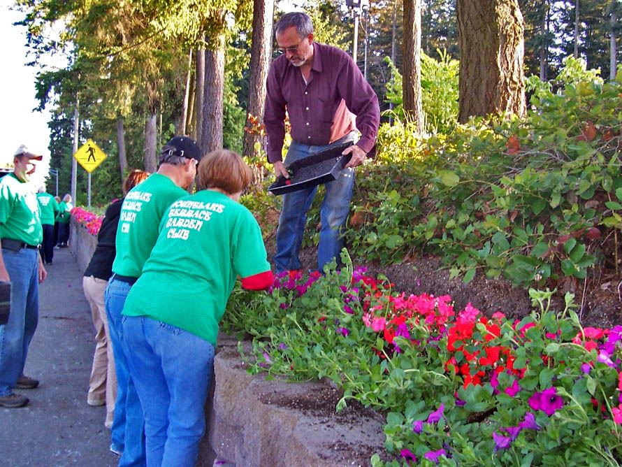 Members of the Garden Club plant flowers at the Library.